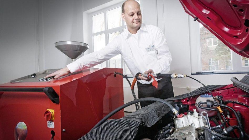 Unternehmer Kemper bei der Ölreinigung an einem Pkw