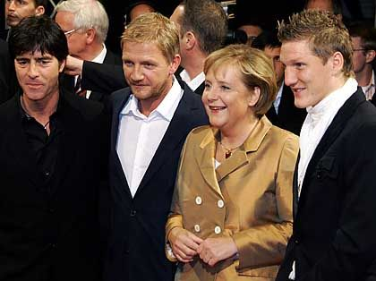 """Director Sönke Wortmann, German Chancellor Angela Merkel and player Sebastian Schweinsteiger pose for the media during the red carpet premiere of the film """"Germany: A summer fairy tale."""""""
