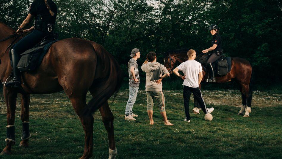 Coronamaßnahme: Eine Polizistin kontrolliert drei Fußballspieler in einem Park