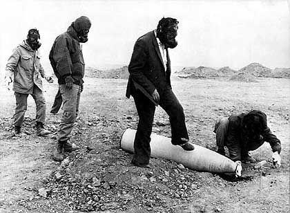 Mit Gasmasken ausgerüstete Uno-Mitarbeiter untersuchen während des Iran-Irak-Krieges eine vom Irak abgefeuerte Chemiebombe