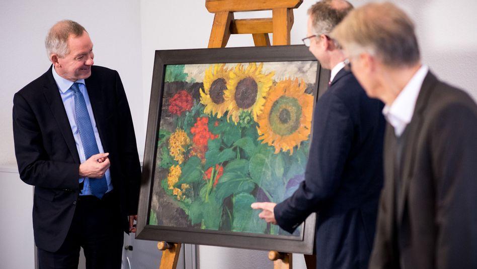 """NDR-Intendant Lutz Marmor (l.) und zwei Mitarbeiter neben dem Ölbild """"Sonnenblumen"""""""