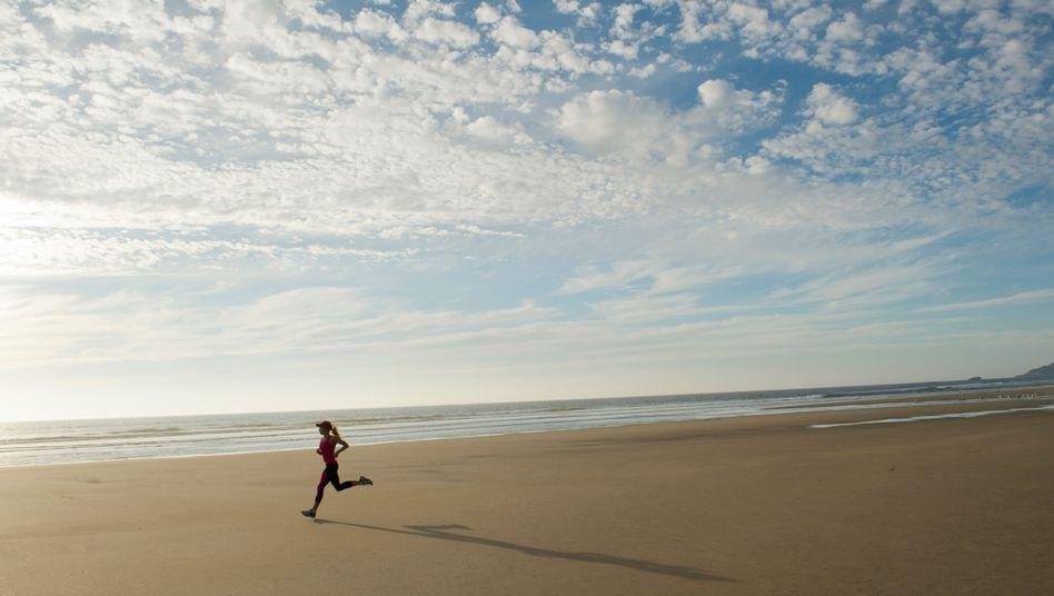 Läuferin am Strand: Das Training auf den Zyklus abzustimmen, kann auch für Freizeitsportlerinnen interessant sein