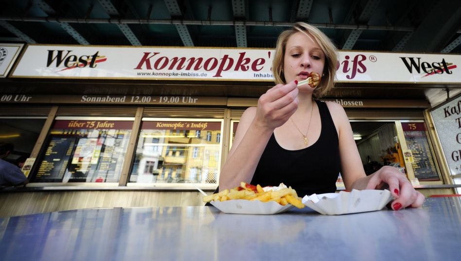 A woman enjoys currywurst and fries outside the Konnopke's sausage stand.