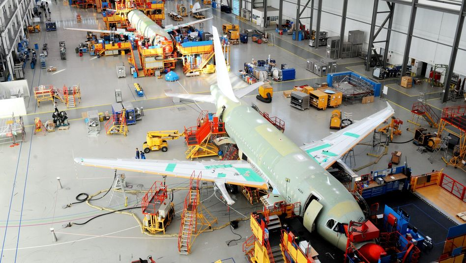 Employees work on the construction of an Airbus A320 aircraft at the EADS plant in Hamburg, Germany.