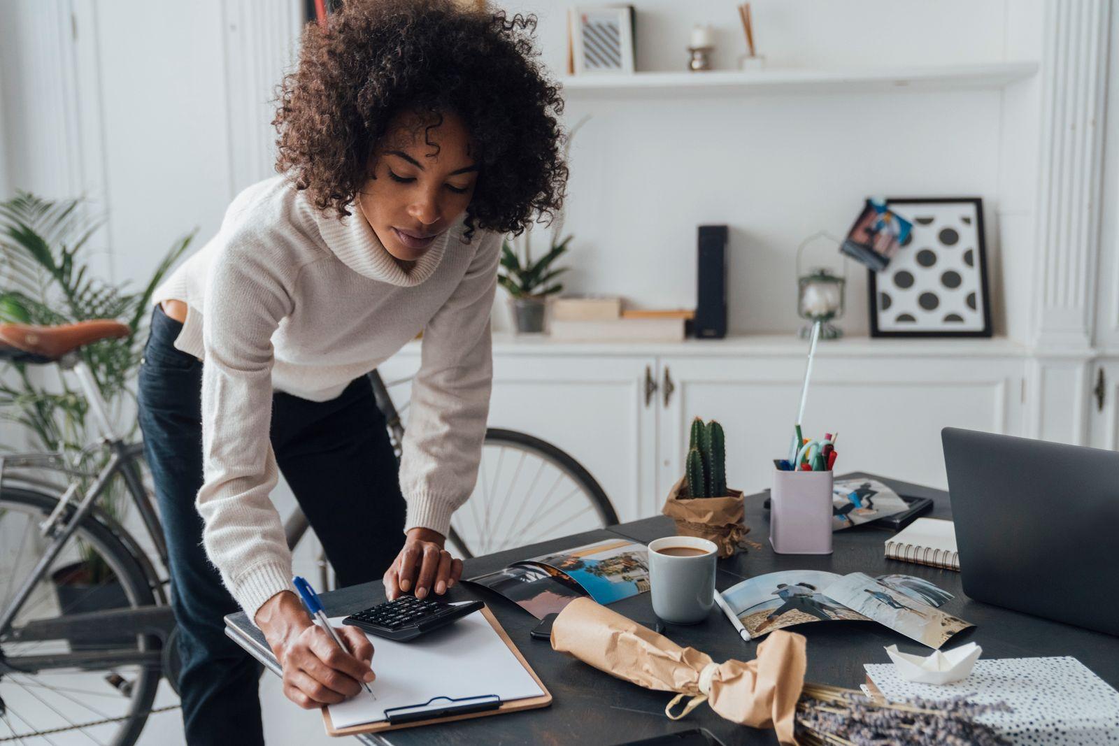 Freelancer standing at hert desk, using calculater, taking notes