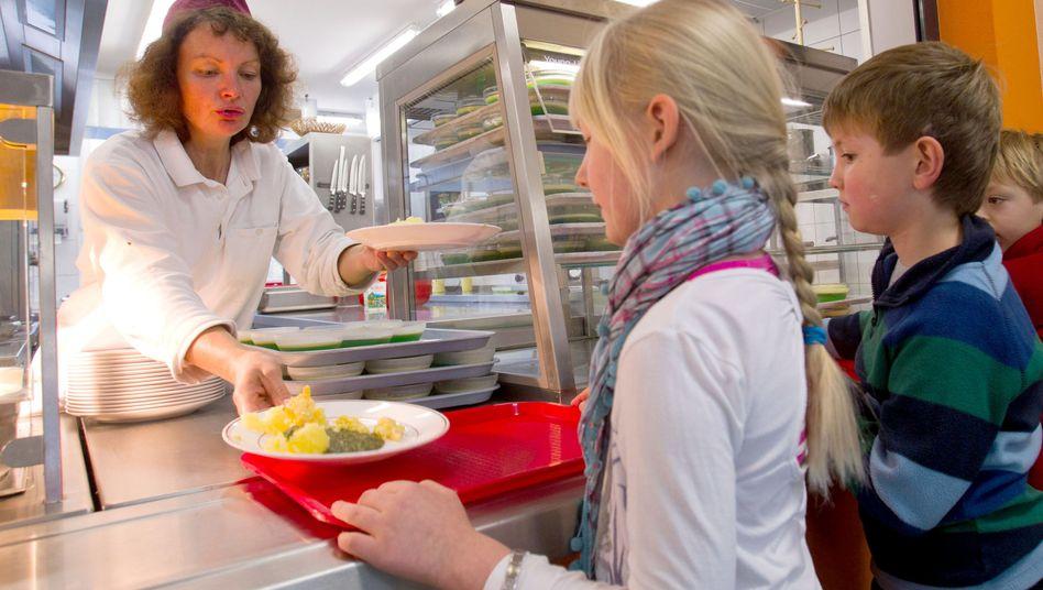 Erstklässler holen sich in ihrer Grundschule ein Mittagessen: Was kostet gute Qualität?