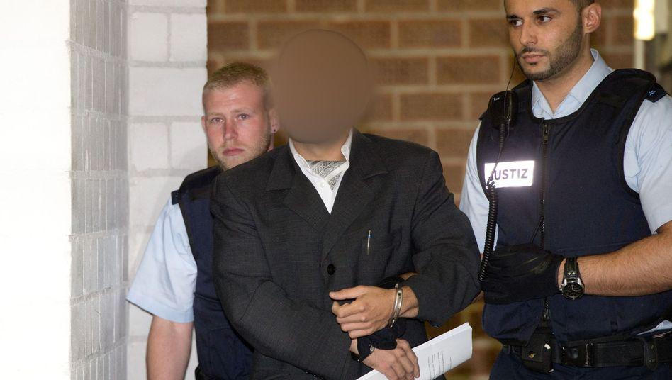 Prozessbeginn in Stuttgart: Einer der drei Angeklagten wird in den Gerichtssaal gebracht