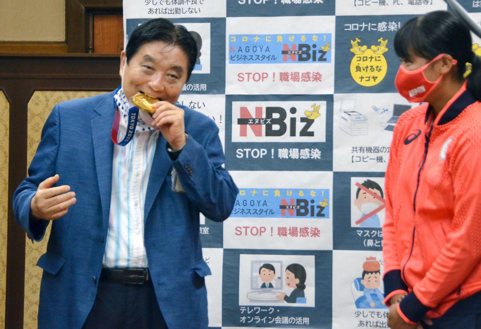 Nagoya city Mayor Takashi Kawamura bites the Tokyo 2020 Olympic Games gold medal of the softball athlete Miu Goto in Nagoya, Japan