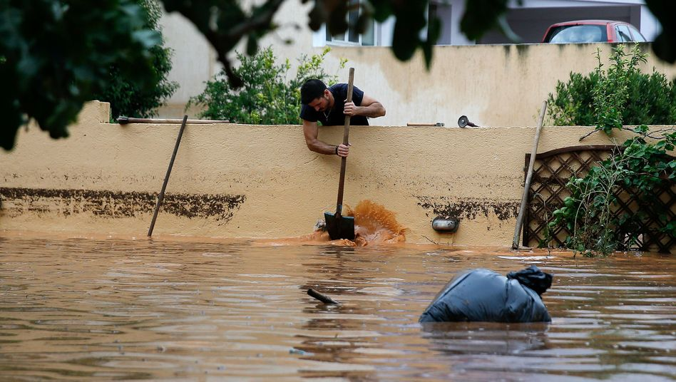 A man removes water from the yard of a house, following flash floods which hit the town of Magoula, Greece, June 27, 2018. REUTERS/Costas Baltas