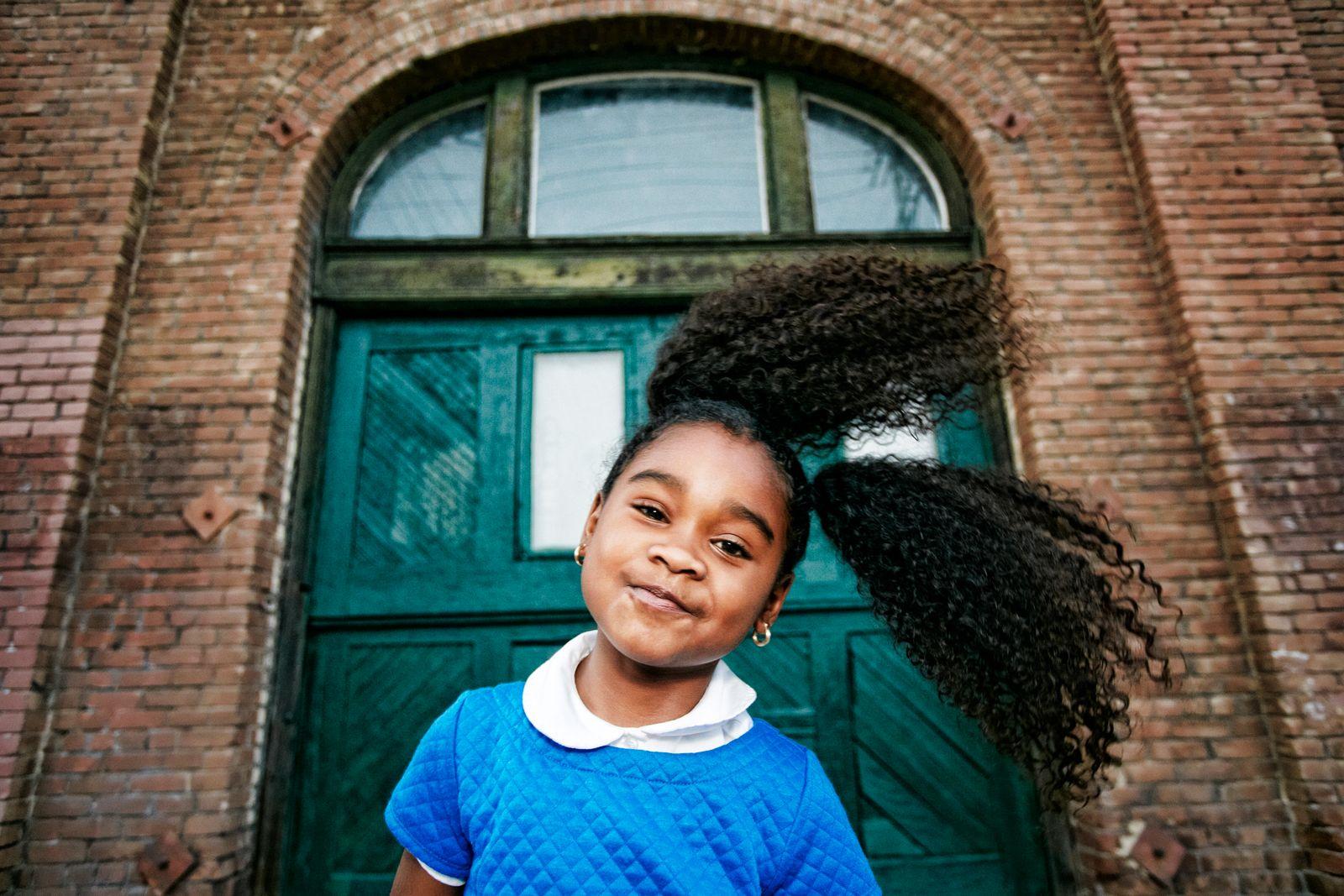 Smiling Black girl tossing hair