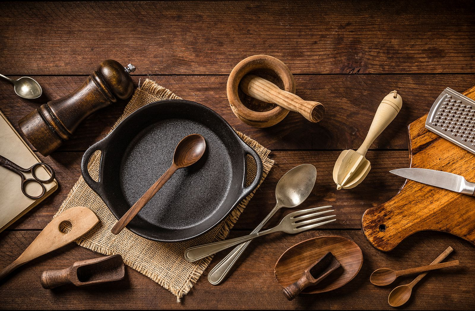 Various kinds of rustic kitchen utensils on a wooden plank