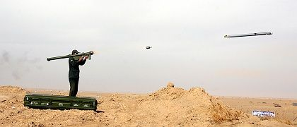 A member of Iran's elite Revolutionary Guard fires a rocket during a maneuver in a central desert area of Iran in 2006.