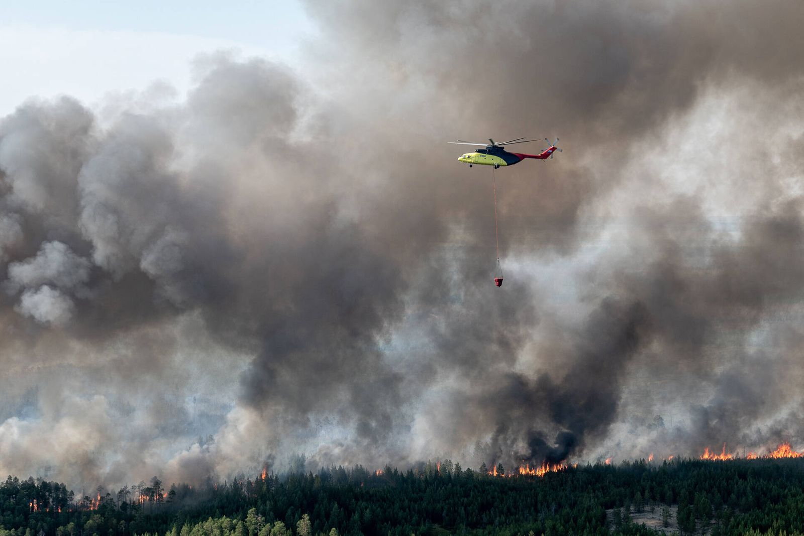 KHANTY-MANSI AUTONOMOUS AREA, RUSSIA - JULY 21, 2020: A helicopter battles a wildfire in the taiga in Sovetsky District