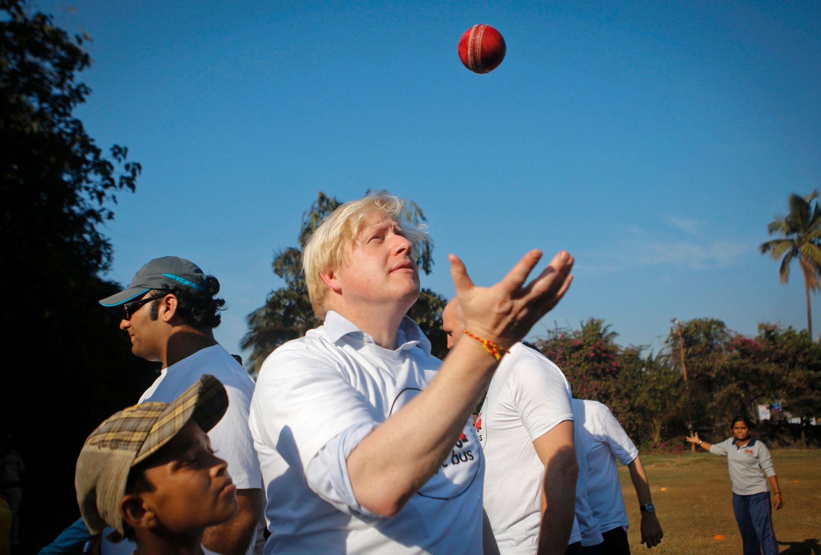 London Mayor Johnson throws a cricket ball before playing games with underprivileged children in Mumbai
