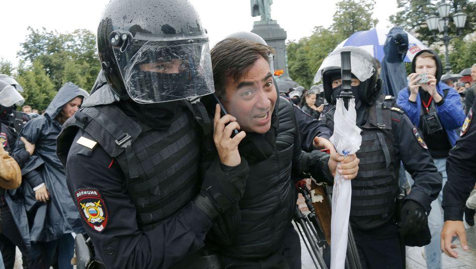 Ein Demonstrant wird von der Polizei in Moskau abgeführt