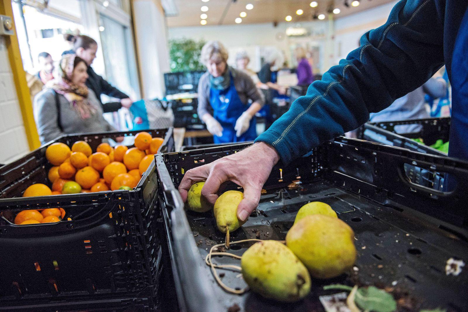 Ehrenamtliche Helfer der Frankfurter Tafel geben von Supermaerkten gespendete Lebensmittel aus im Au
