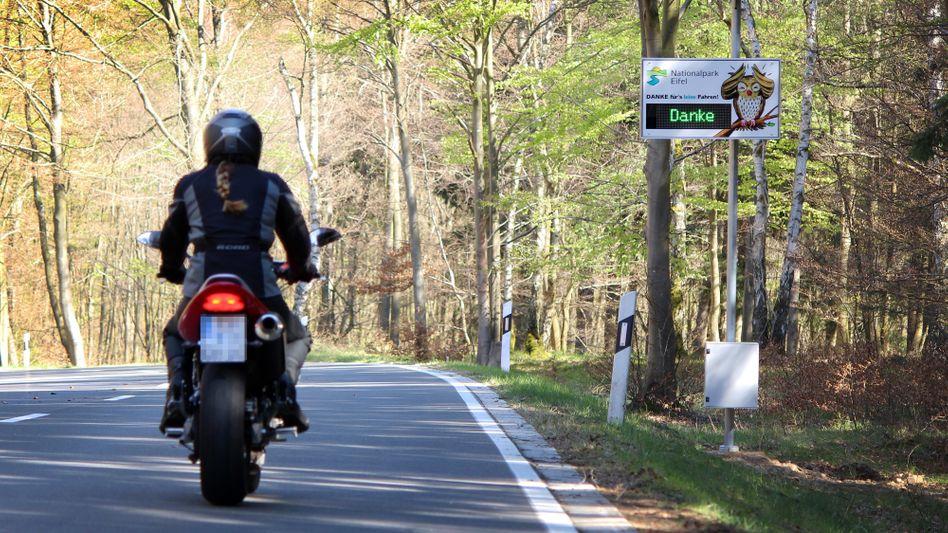 Lärmdisplays wie hier im nordrhein-westfälischen Simmerath sollen helfen, Motorgeräusche zu reduzieren. Motorradpolizist Volker Heinen ist ebenfalls in der Eifel im Einsatz.