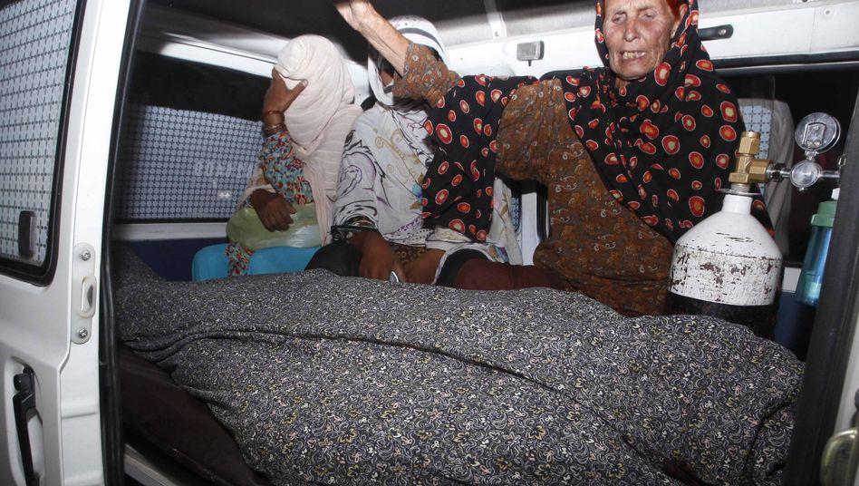 Lahore: Angehörige mit dem umhüllten Leichnam von Farzana
