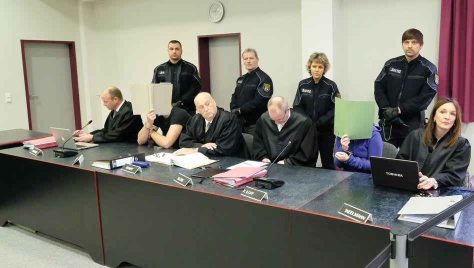 Angeklagte mit Anwälten im Gerichtssaal