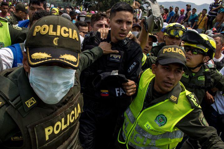Kolumbianische Polizisten halten einen venezolanischen Kollegen fest, der die Grenze überquert hatte