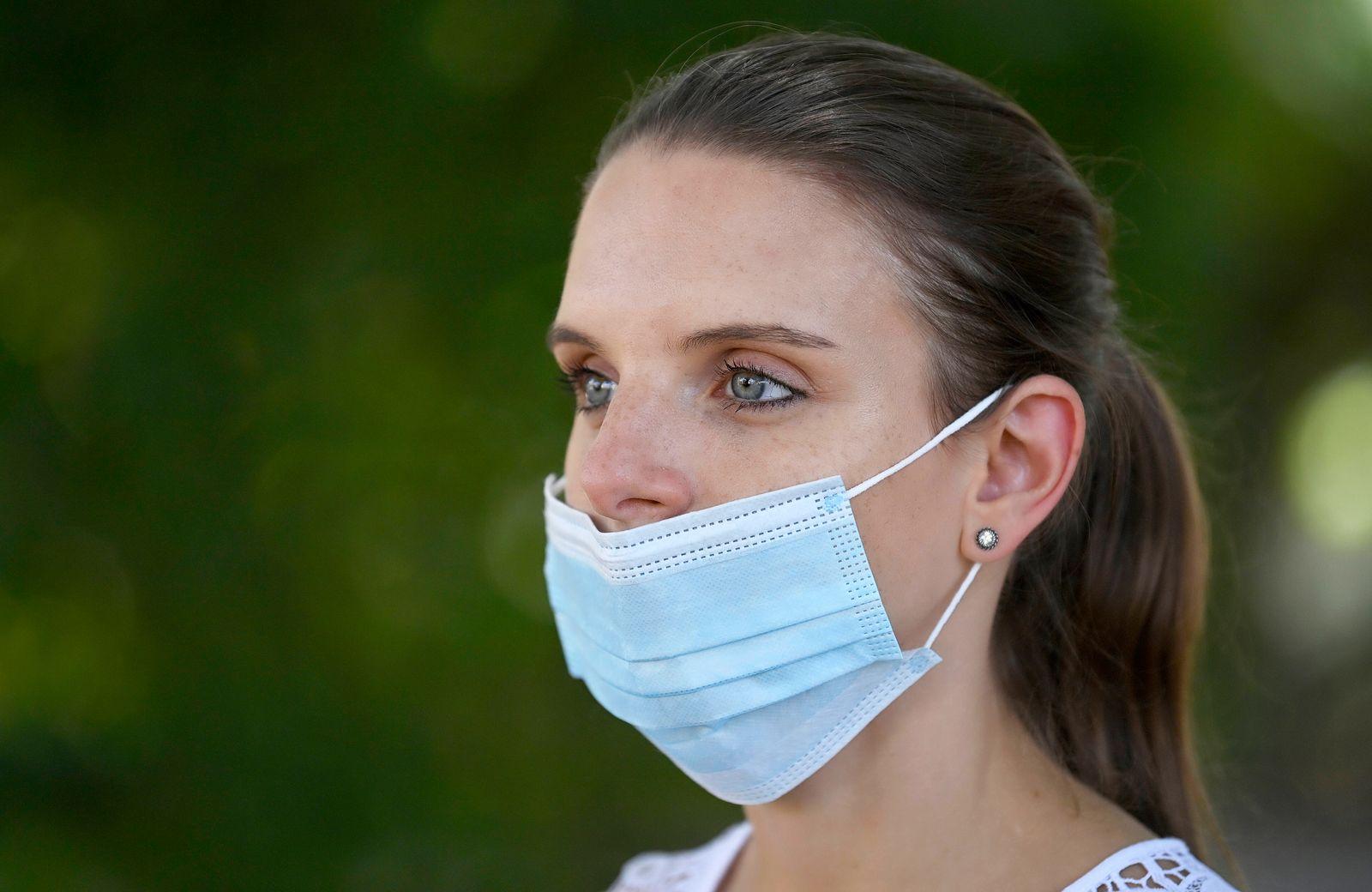 Frau tr?gt Mundschutzmaske unter der Nase, Portrait, Corona-Krise, Deutschland Coronavirus *** Woman wearing a face mask