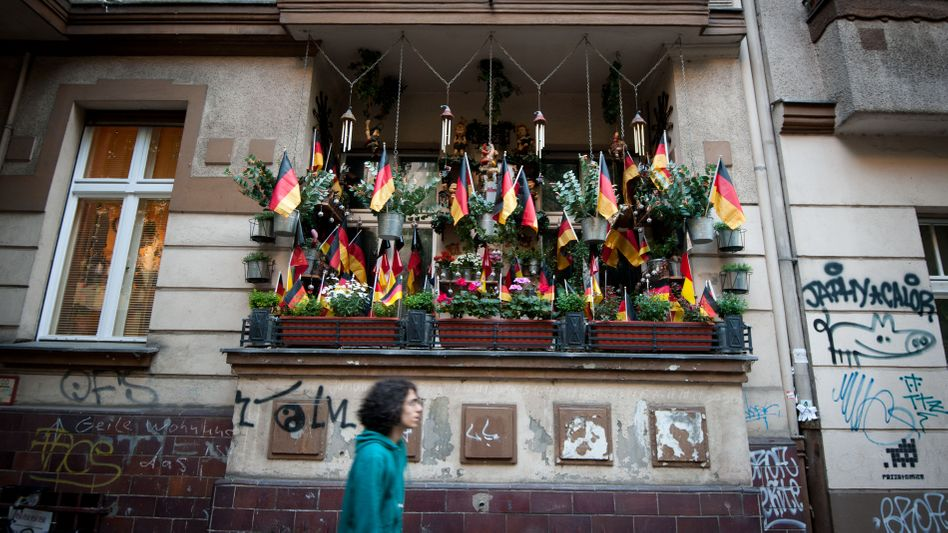 A pedestrian in Berlin walks by an apartment balcony filled with German flags: Is Germany going down the drain?