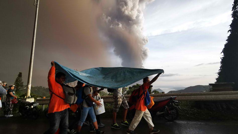 Rauch über den Philippinen: Anwohner schützen sich in Tagaytay vor Ascheregen aus dem Vulkan Taal