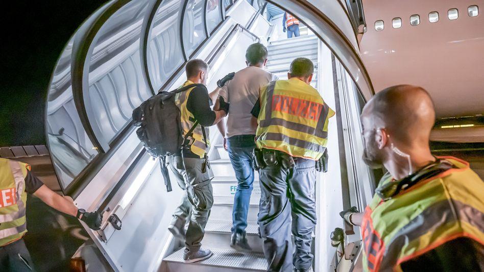 Polizisten begleiten einen Afghanen bei einem früheren Abschiebeflug in Leipzig (Archivbild von 2019)