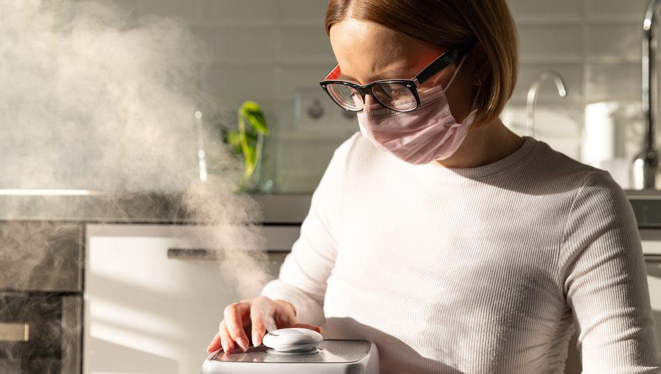 Frau mit Mund-Nasen-Schutz und Luftbefeuchter