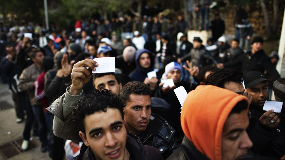 Tunisians line up outside an immigrant detention center on Lampedusa on Monday.
