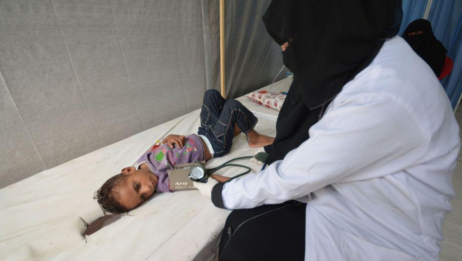 Eine Krankenschwester kümmert sich um einen mit Cholera infizierten Jungen