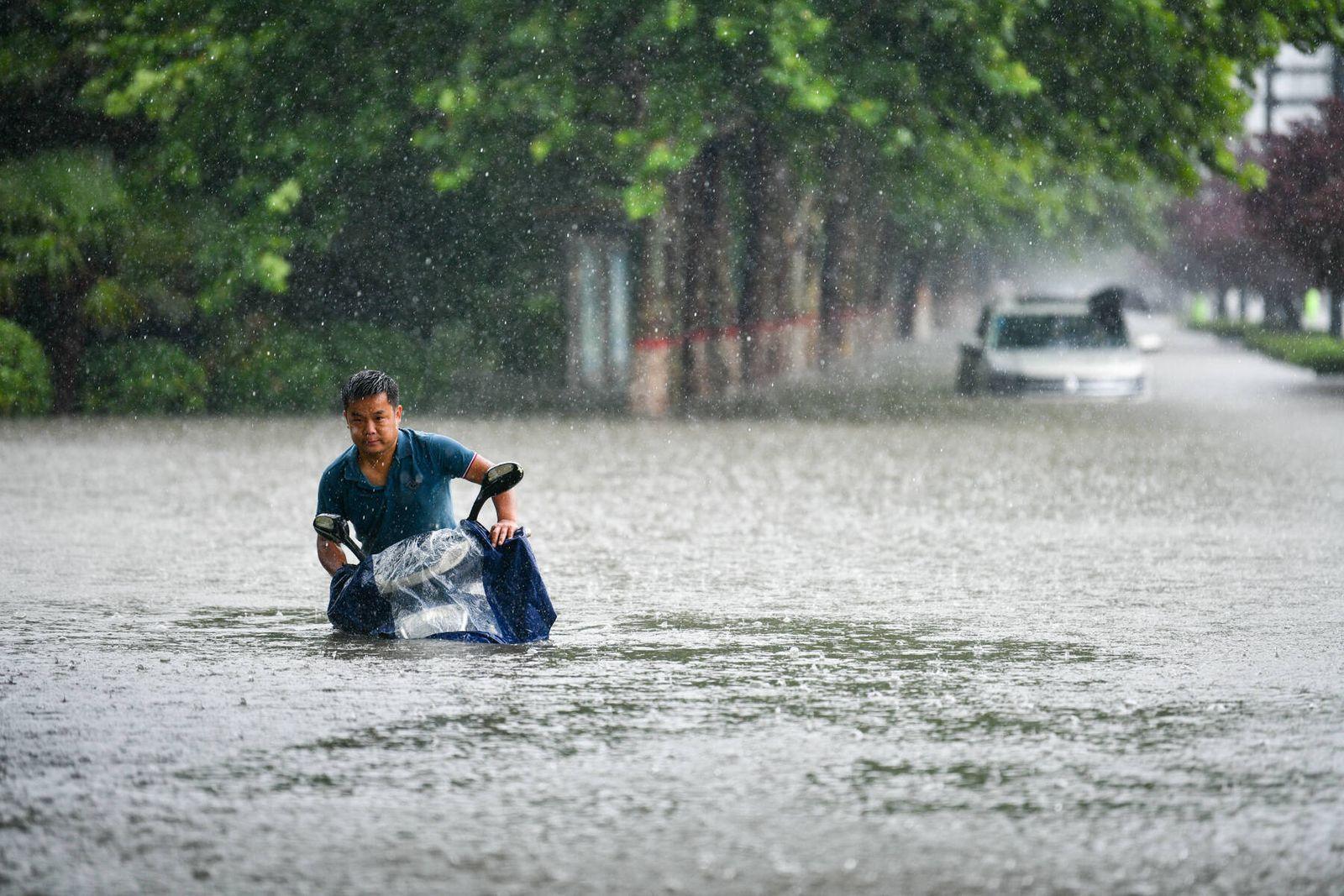 (210720) -- ZHENGZHOU, July 20, 2021 -- A man rides on a waterlogged road in Zhengzhou, capital of central China s Hena