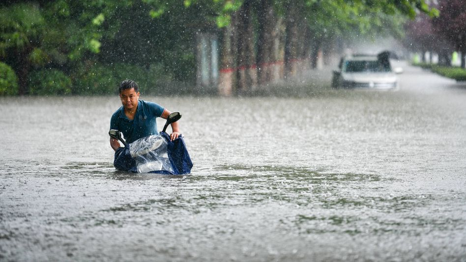 Ein Mann versucht, seinen Roller durch die Wassermassen in Zhengzhou zu schieben