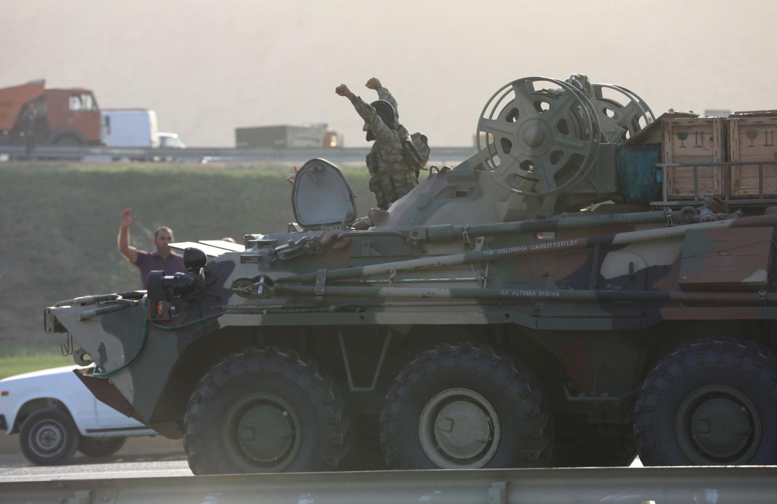 An Azerbaijani service member drives an armoured carrier in Baku