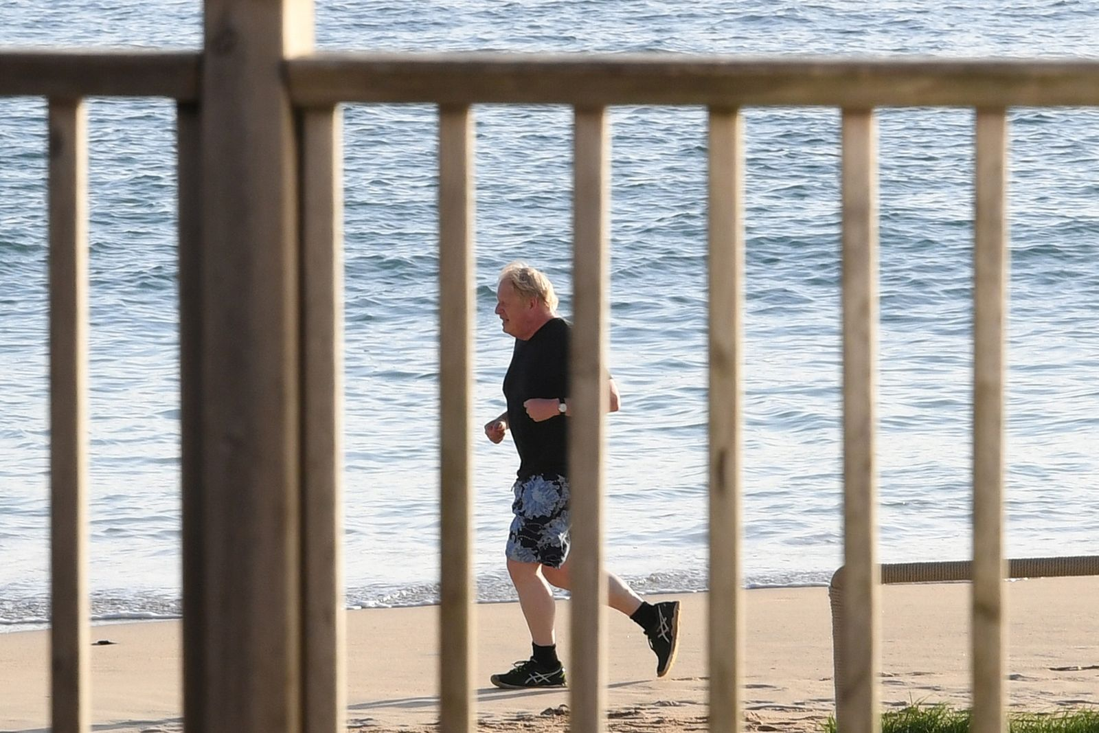 Britain's Prime Minister Johnson runs along the beach in Carbis Bay