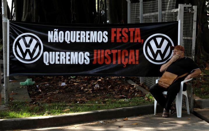 """Ein Ex-VW-Arbeiter demonstriert vor dem Fabrik-Gebäude. """"Wir wollen keine Party, wir wollen Gerechtigkeit"""", steht auf dem Plakat."""