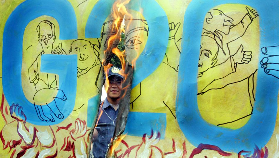 Protesters burn a placard during an anti-G-20 rally on Tuesday, Sept. 22, in Manila, Philippines.