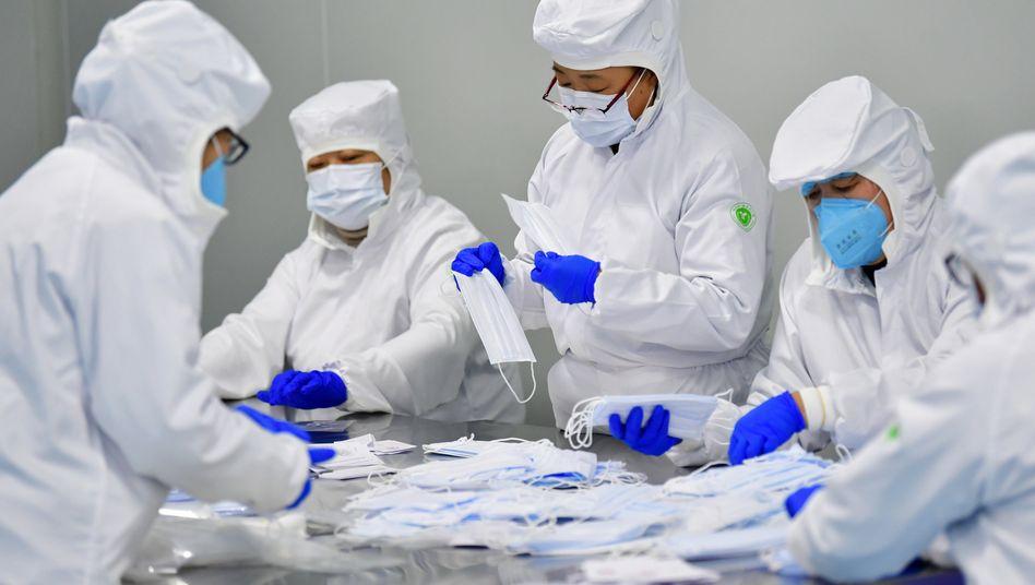 Arbeiter in China verpacken Mundschutzmasken