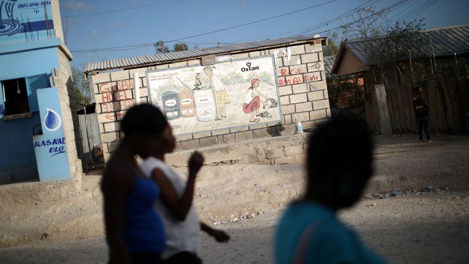 Frauen in Haiti vor einem Oxfam-Hinweis an einer Wand