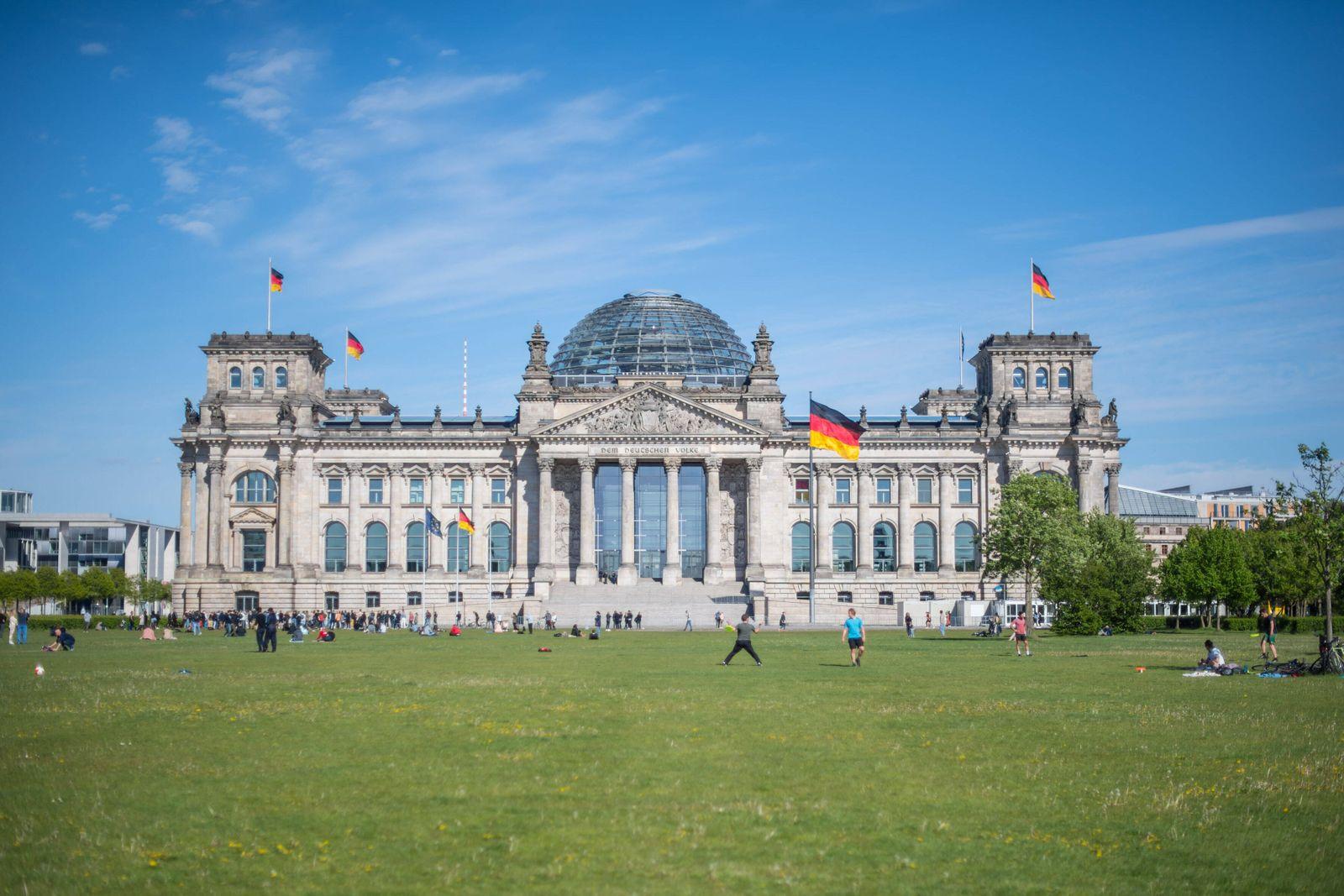 Berlin Fruehlingswetter Platz der Republik Menschen geniessen das gute Fruehlingswetter auf der Wiese vor dem Reichstag