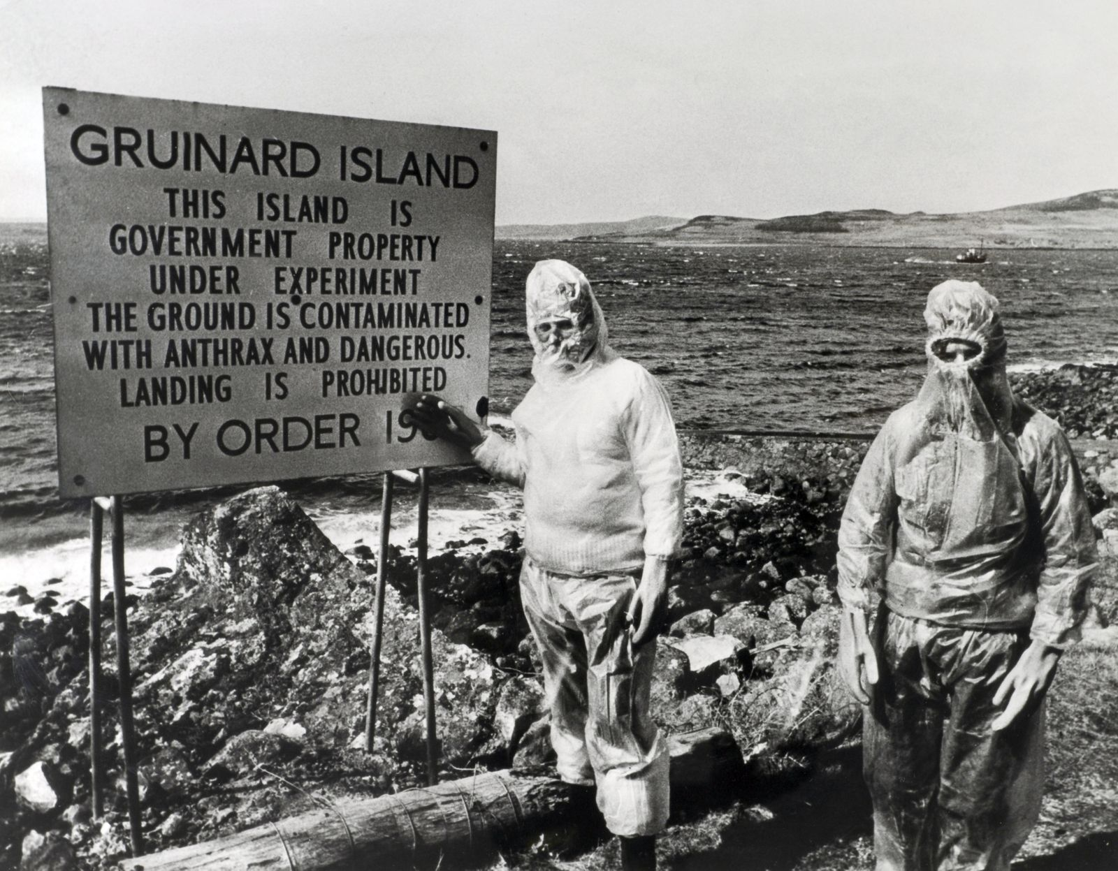 War and Conflict. World War Two. Scotland. Circa 1940's. Two men, wearing protective clothes stand by a sign on Gruinard Island. This small island off the Scottish coast has been quarantined following British Governments tests with Biological warfare agen