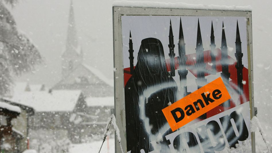 "A sticker saying ""Thank You"" is posted on a controversial placard that was used by supporters of Switzerland's campaign to ban minarets."