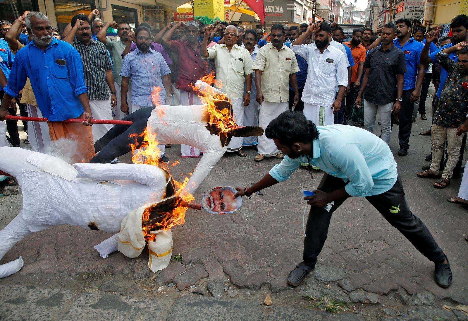 Supporters of Centre of India Trade Union burn effigies depicting U.S President Donald Trump and India's Prime Minister Narendra Modi during a protest against Trump's visit to India, in Kochi