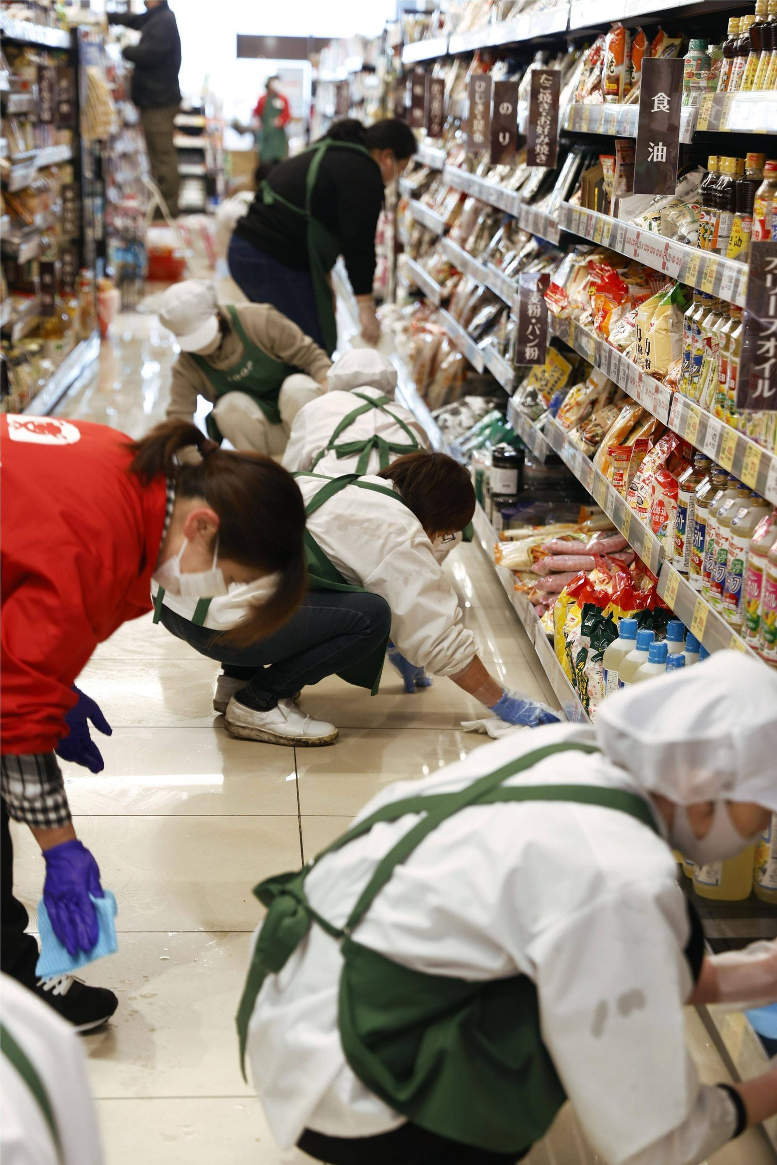 Strong quake hits northeastern Japan Workers at a supermarket in Kunimi, Fukushima Prefecture, wipe up oil spilled on t