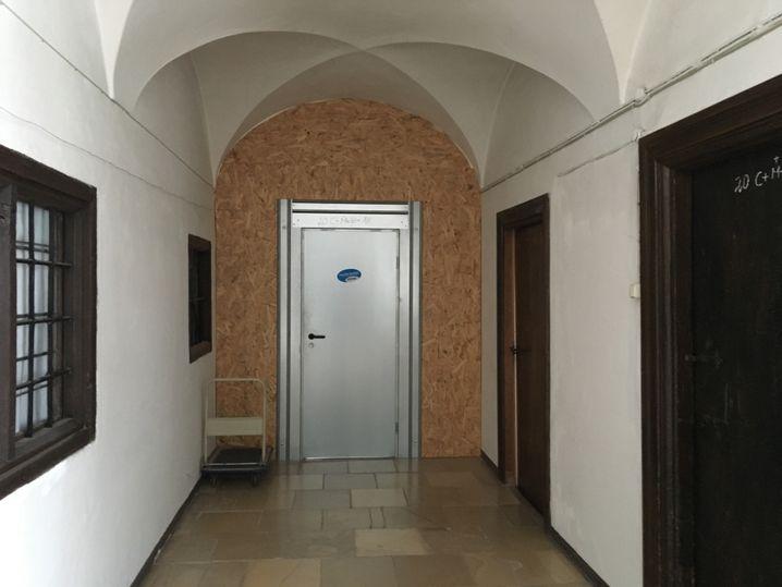 Eine Wand aus Sperrholz verperrt den Weg zum Wohntrakt