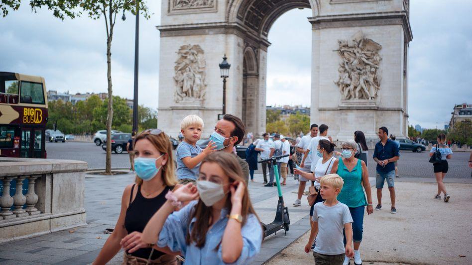 Touristen mit Schutzmasken auf der Champs-Elysees in Paris