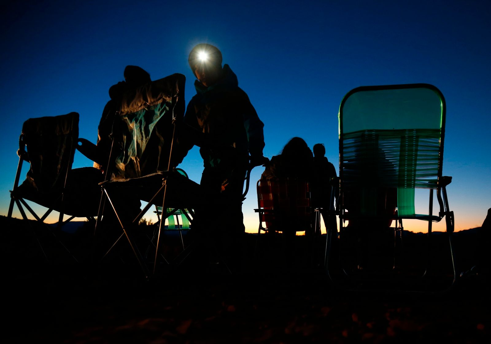 Spectators set up lawn chairs in hopes of seeing an UFO during an UFO tour in the desert outside Sedona, Arizona