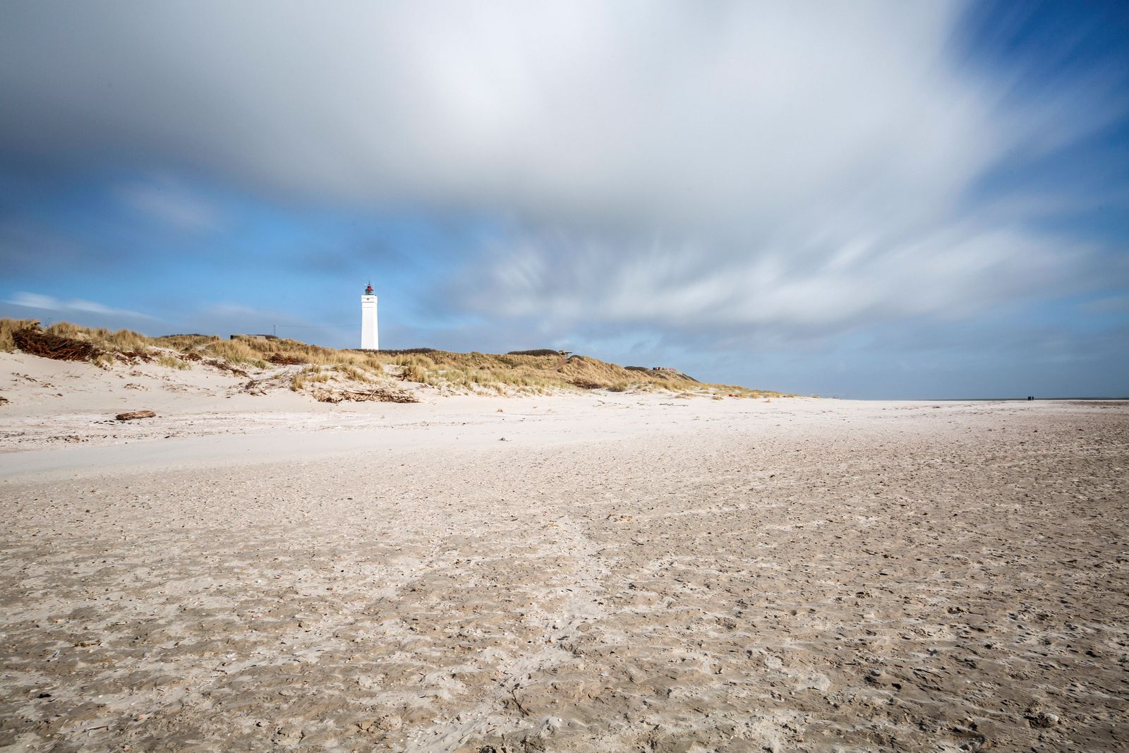 Denmark, Romo, Blavand, Clouds over sandy coastal beach with lighthouse in background ASCF01184