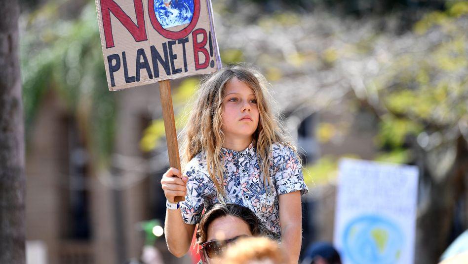 Ein Mädchen hält in Brisbane, Australien während einer Demonstration ein Schild hoch
