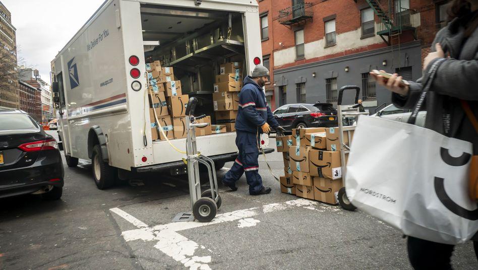Ein Paketauslieferer in New York lädt Amazon-Pakete aus seinem Transporter aus